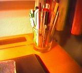 Stifte im Glas auf Schreibtisch