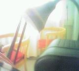 Lautsprecher und Lampe vor zwei Holzsesseln mit rotem Sitzkissen