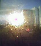 Himmel und Hochhaus hinter tropfenbedeckter Fensterscheibe, Licht bricht sich in Tropfen