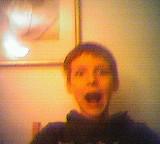Junge mit offenem Mund und Grimasse vor Wand mit Bild